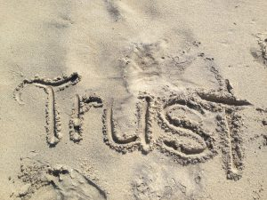 Trust written in sand on the beach.
