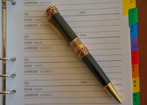 An address book open with an ornate pen on top of it.