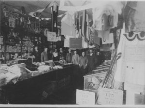 A very old picture of the inside of a store with the workers inside, all in black and white.