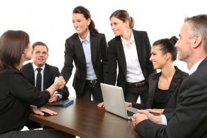 Business people around a desk shaking hands.