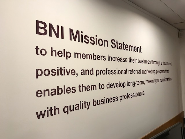 The BNI mission statement written on the wall.