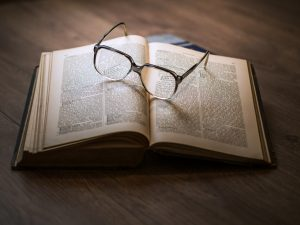 An open book with a pair of eyeglasses on it.