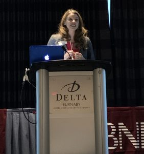 A woman with her BNI name badge on in front of a podium.