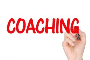A hand writing the word coaching.