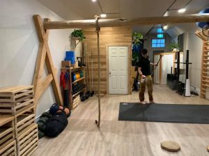 A gym with a rope tied around a wooden structure to use in a workout.