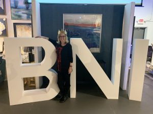 A large BNI sign with a woman standing in front of it.