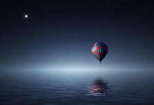 A hot air balloon over the water in the night sky.