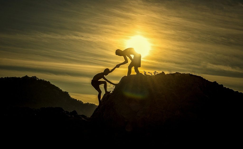 Two people on a mountain and one helping another up the hill.