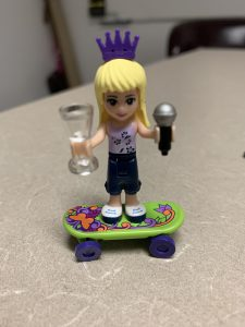 A figurine of a girl with a crown riding a skateboard.