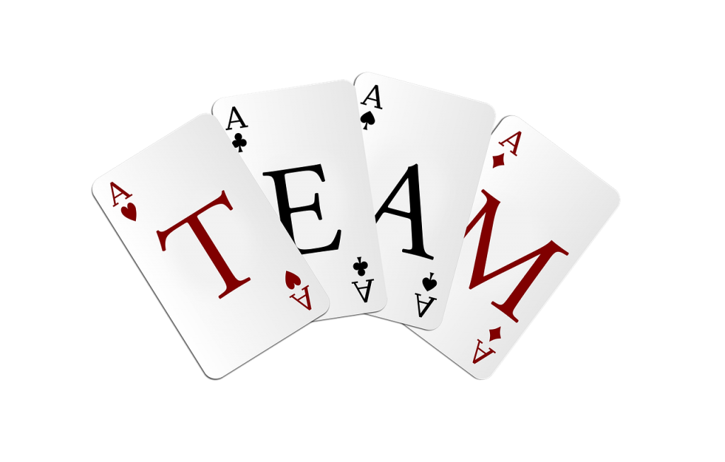 A group of playing cards spelling the work team.