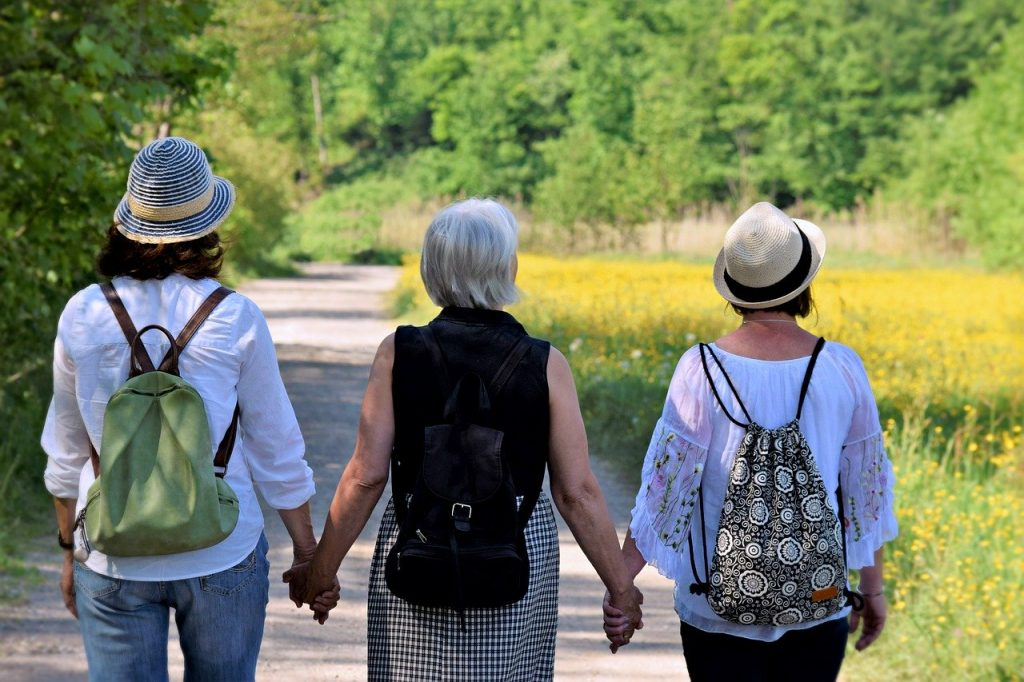 Three woman walking holding hands in support.