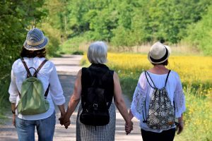 Three woman walking together and holding hands.