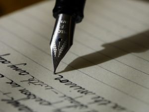 A pen writing on a piece of paper.