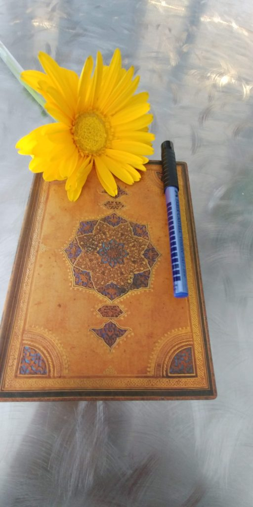 A book with a yellow flower and pen.