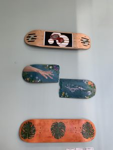 Three skateboards painted on the bottom side hanging on the wall.   One of the skateboards is cut in half.