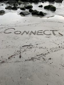 The word connect written in sand on the beach.