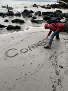 A woman bending over and writing the word connect in the sand on the beach.