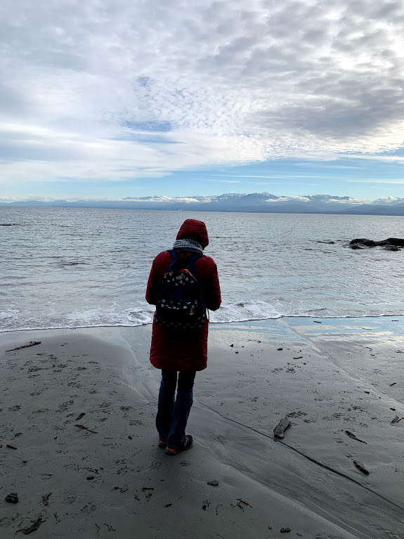 A woman walking on the beach with a red jacket on.