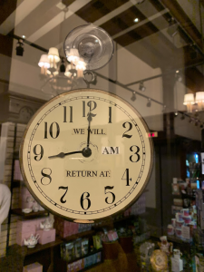 A clock hanging up in a store front.