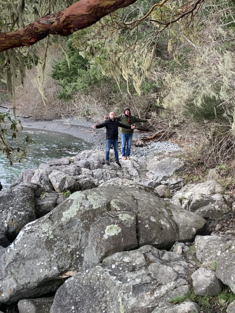Two men on a rock with their arms outstretched.
