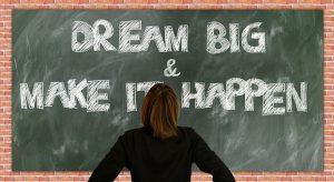 Dream big and make it happen written on a chalkboard.