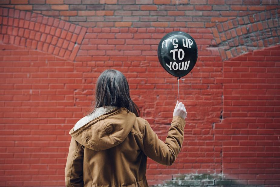 A girl holding a black balloon saying its up to you!!