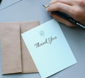 A note saying Thank You with a pencil in someones hand.