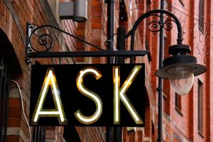 The ask sign on a lamppost  by buildings.