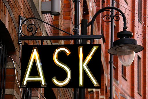 A sign that says ASK hanging up by a light post.