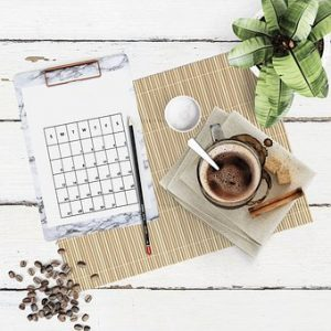 A calendar with a pencil, coffee and a plant on the table.