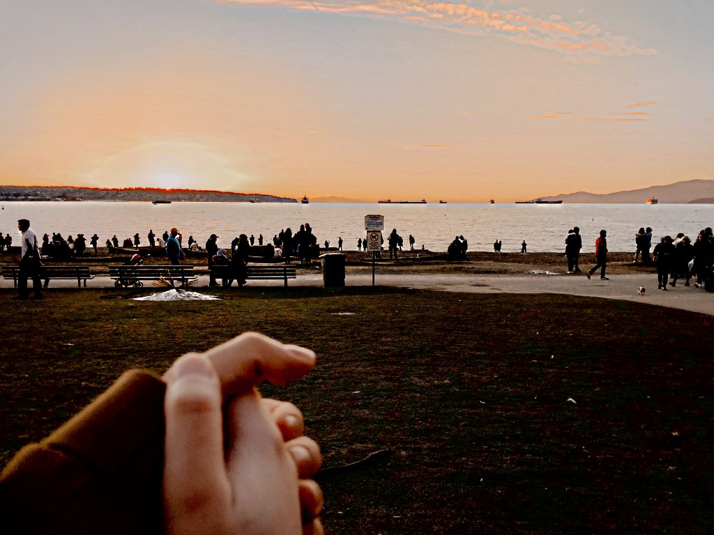 Two people holding hands by the water.